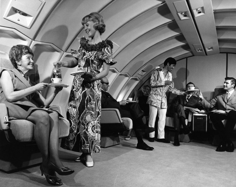 UAL Publicity Shot: Stewardess with Passenger, serving food.  Likely on a Hawaii flight, given clothing.  Possibly 1970s.  United Airlines Photograph #2670-88