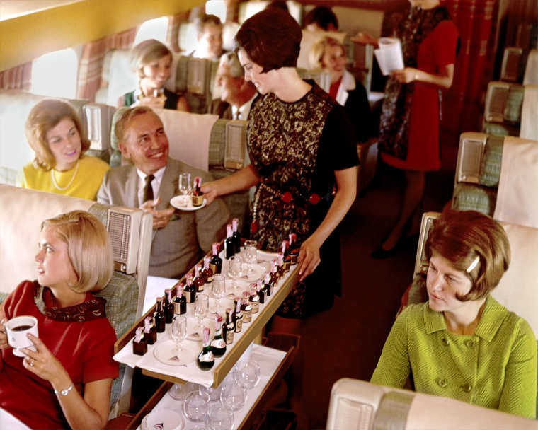Flight attendant serving alcohol from serving cart. 1968-1970 winter uniform.