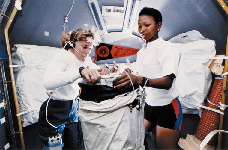 Astronauts Dr. N. Jan Davis, left, and Dr. Mae C. Jemison prepare to deploy the lower body negative pressure apparatus on Sept. 15, 1992. Photo taken in the science module aboard the Earth-orbiting Space Shuttle Endeavor during STS-47. The Spacelab-J mission was a joint effort between Japan and the United States.