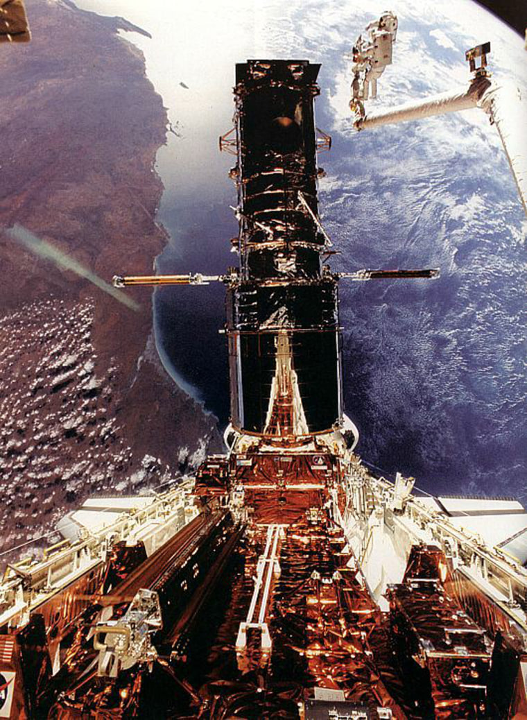 In December of 1993 astronauts Story Musgrave and Jeffrey Hoffman performed the orbiting repairmans' ballet 400 miles above the Earth. They are seen in this photo perched at the end of the Space Shuttle Endeavour's robotic arm making final repairs to the four story tall Hubble Space Telescope. The coast line of western Australia is visible below. The complex and highly successful repair mission allowed HST to see into the Universe with unprecedented clarity.