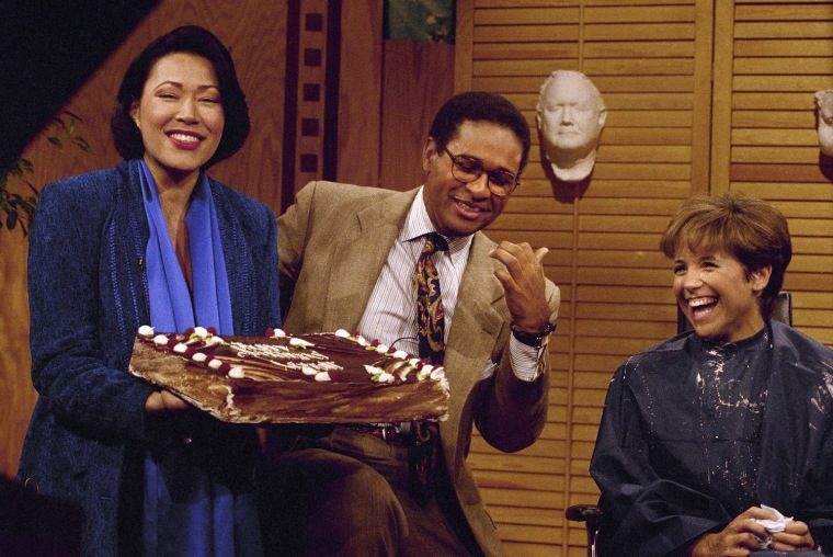 """NBC-TV  """"Today Show"""" co-host Bryant Gumbel is presented a suprise birthday cake, minus the traditional candles, on the air September 29, 1992  in New York from news anchor Ann Curry.   Co-host Katie Couric, right, watches.   Gumbel is turning 44.   (AP Photo/Richard Drew)"""