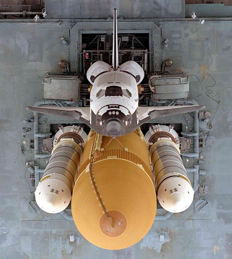 The Space Shuttle Atlantis begins the slow journey to Launch Pad 39A from the Vehicle Assembly Building (VAB) in preparation for the launch of STS-79 in 16 September 1996. This dramatic view looking directly down onto the shuttle stack atop the Mobile Launcher Platform (MLP) and crawler-transporter was taken from the VAB roof approximately 525 feet (160 meters) above the ground. In view are the Orbiter, orange External Tank and twin white Solid Rocket Boosters.