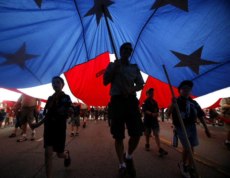 Image: Boy Scouts of America and Cub Scout troops carry a large American flag during the LibertyFest Fourth of July parade in Edmond, Okla.