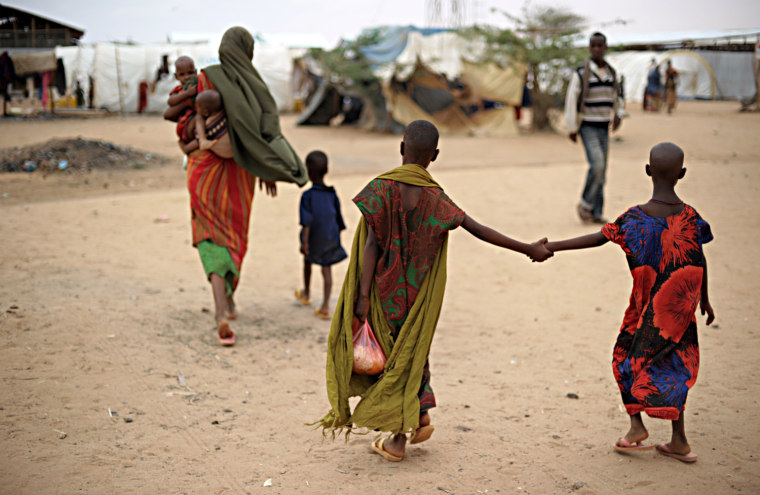 Image: Farhiya (centre) holds her 7-year-old sister Suladan by the hand as they follow their mother and brothers at the reception center of the Dolo Ado refugee camp near the Ethiopia-Somalia border