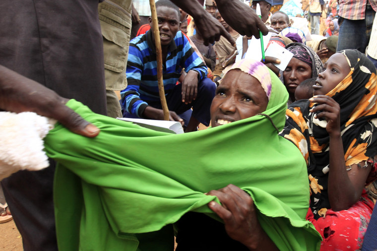 Image: A newly arrived Somali refugee is forced out of the queue outside a reception centre in the Ifo 2 refugee camp in Dadaab