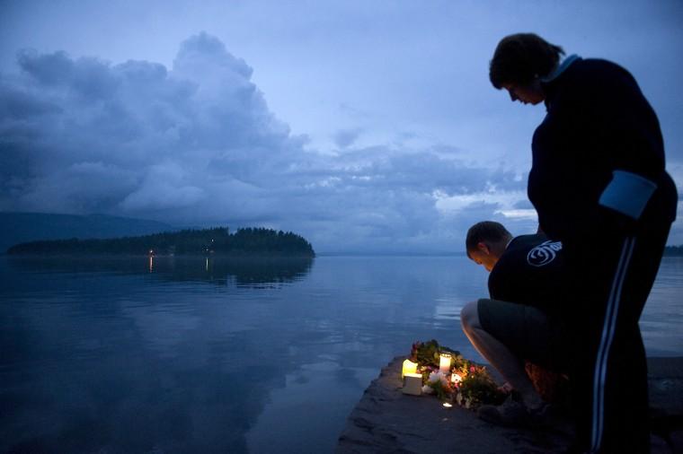 Image: People light candles near Utoeya island