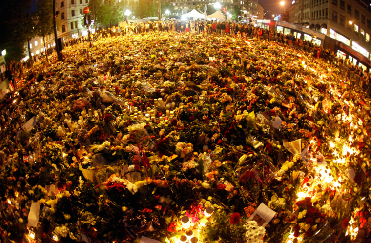 Image: A sea of flowers and lit candles are placed in memory of those killed in Friday's bomb and shooting attack in front of Oslo Cathedral