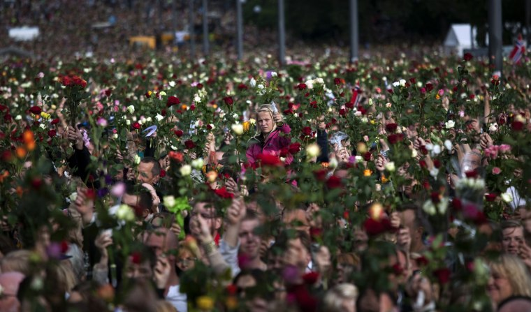 "Image: People gather outside Oslo City Hall to participate in a ""rose march"" in memory of the victims of Friday's bomb attack and shooting massacre"