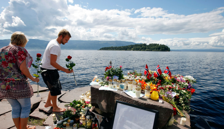 Image: People pay their respects for the victims in last Friday's killing spree and bomb attack, at a temporary memorial site on the shore in front of Utoeya island