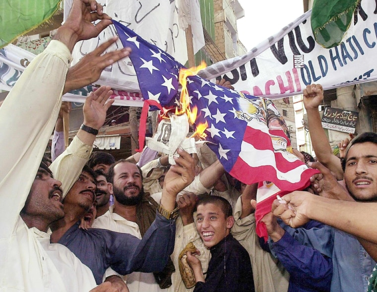 Activists of a right-wing group burn the US flag  in southern Karachi on 17 September 2001, to show their anger over the imminent attacks of the US on Afghanistan by using Pakistan's land. Local police arrested at least 24 activists as the holding of such demonstrations has been banned.      AFP PHOTO/Aamir QURESHI