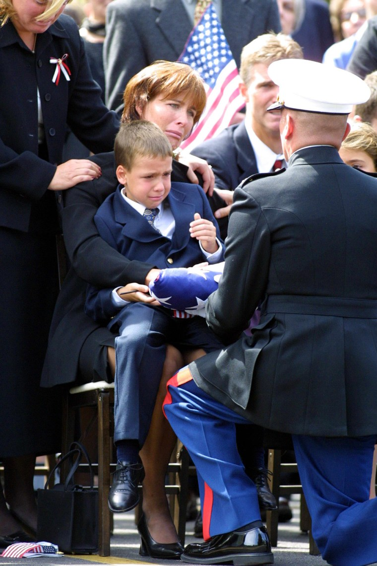 Miriam Horrocks, seated, with her son, Michael, 6, on her lap, is presented with the U.S. Flag by a U.S. Marine Corp honor guard following a funeral mass 17 September 2001 in Media, PA, for her late husband Michael Horrocks 38, who was killed 11 September when the hijacked United Airlines flight 175 that he was co-piloting crashed into the south tower of the World Trade Center in New York City.  Partially visable at far right is Horrocks' daughter, Christa, 9.    AFP PHOTO/ TOM MIHALEK
