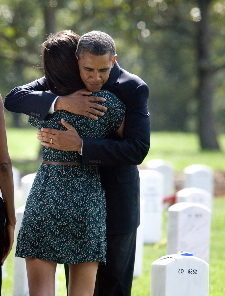 Image: U.S. President Barack Obama hugs a visitor during a visit to Arlington National Cemetery in Washington