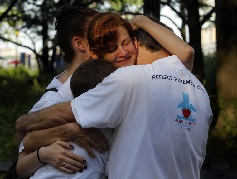 "Image: The Score family hugs after participating in the ""Hand In Hand, Remembering 9/11"" event in Battery Park in New York"