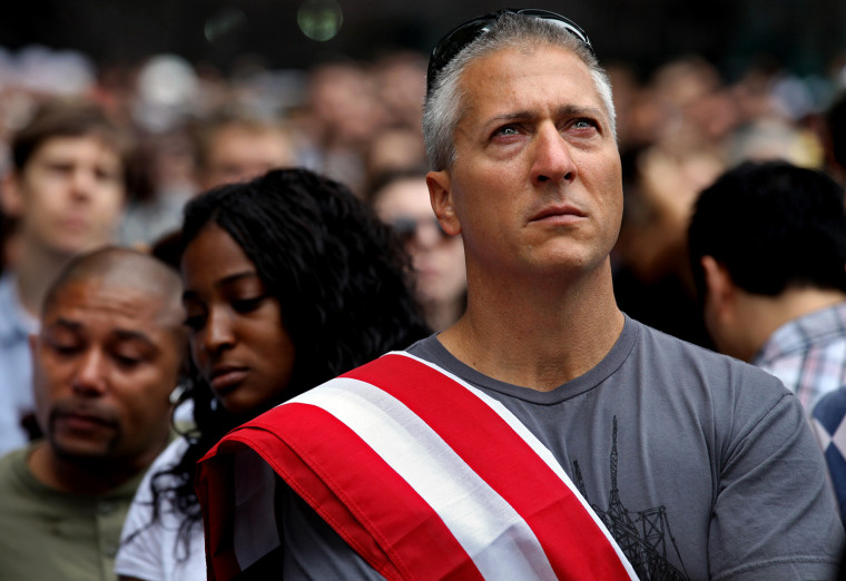 Image: People listen to the 9/11 ceremony at the WTC site in NYC