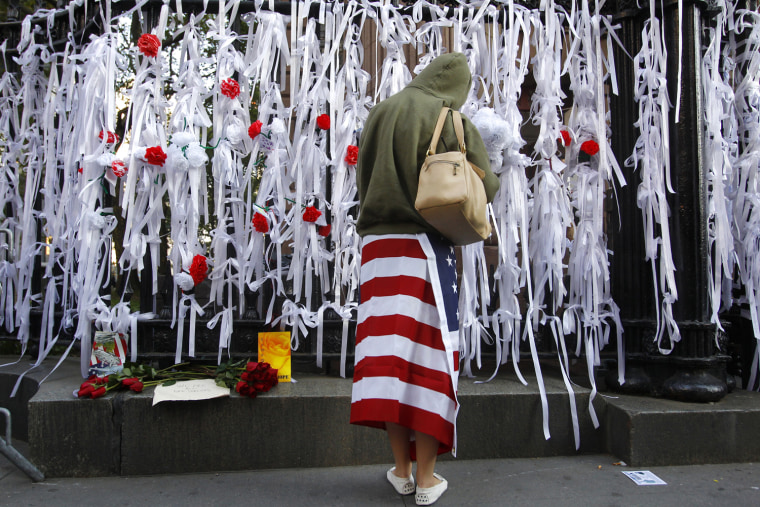 Image: A woman reads ribbons of remembrance on a fence during events marking the 10th anniversary of the 9/11 attacks on the World Trade Center in New York