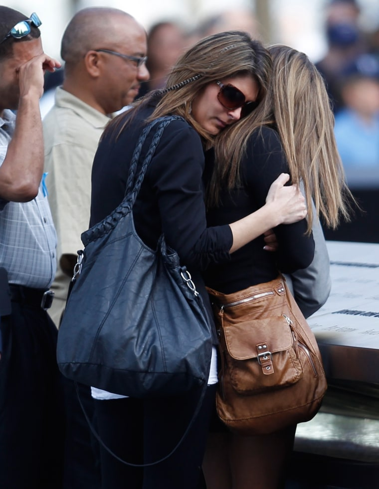 Image: Mourners embrace during tenth anniversary ceremonies at the site of the World Trade Center in New York