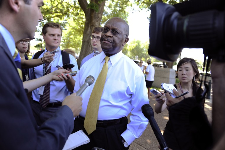 Image: Republican presidential hopeful Herman Cain talks to reporters as dozens of Tea Party supporters rally near the U.S. Capitol against raising the debt limit in Washington