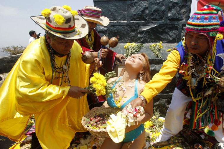 Image: A woman holds an offering of fruits as shamans perform a ritual for good luck for the new year in Lima