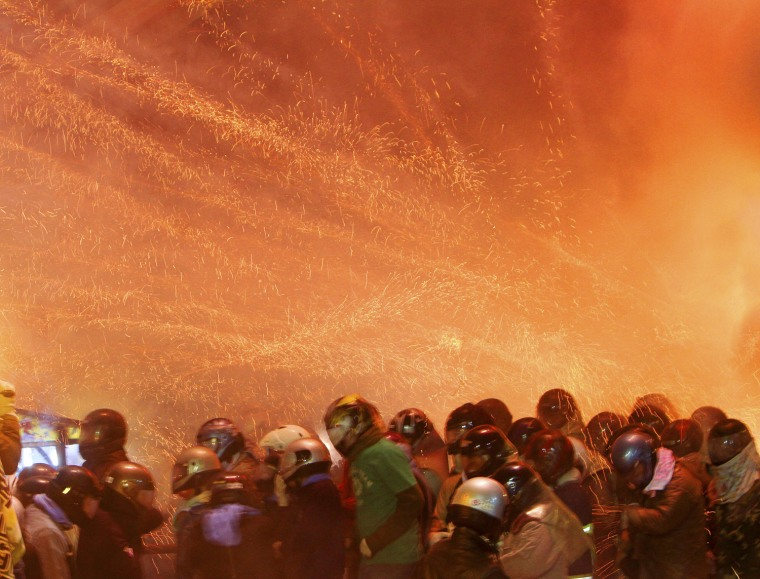 """Image: People get hit by firecrackers during the Yanshui Beehive Rockets Festival, as part of the Chinese Lantern Festival or """"Yuan Xiao Jie"""", in Tainan County"""