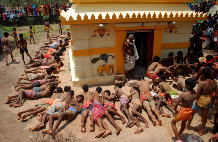 Image: Indian men roll around a temple as they