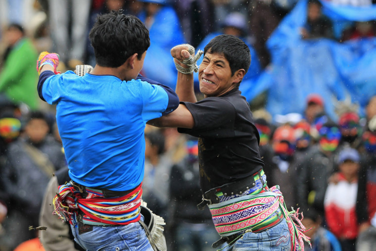 """Image: Andean men participate in a one-on-one fight during the """"Takanakuy"""", a traditional festivity at Chumbivilcas province in Cuzco"""
