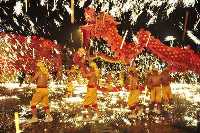 Image: A dragon dance is performed amid fireworks during a Lantern Festival celebration in Chongqing municipality