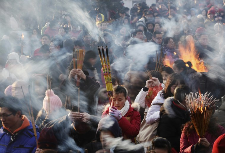 Image: A woman prays for good fortune as she holds burning incense on the first day of the Chinese Lunar New Year in Beijing