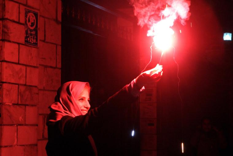 Image: An Iranian woman holds a firecracker in