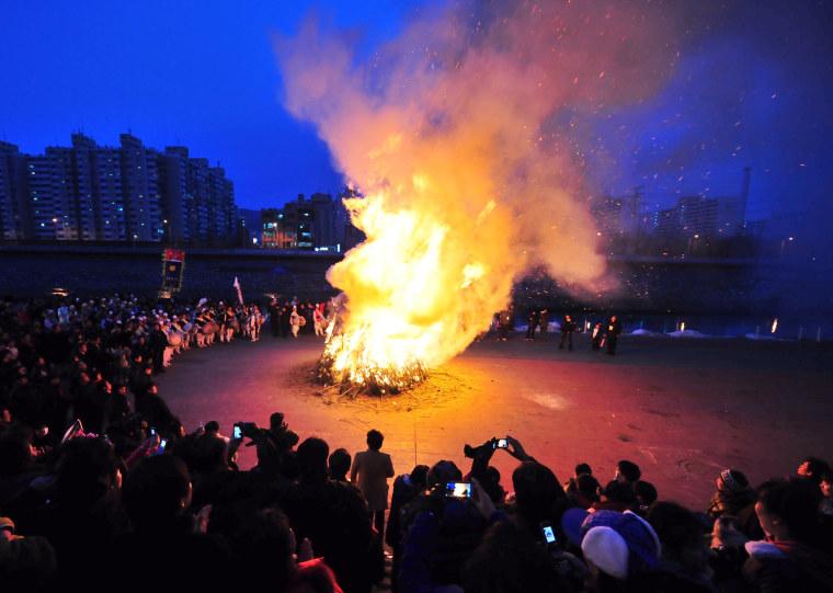 Image: South Koreans gather around a huge bonfi