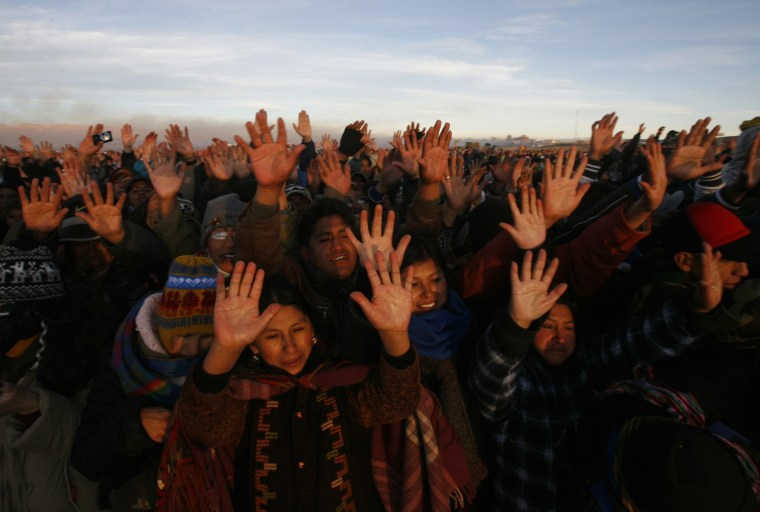 Image: People raise their hands to receive the first beam of the rising sun during the winter solstice ceremony in Tiahunaco