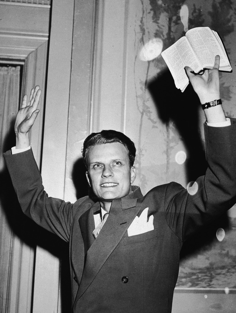 Image: Billy Graham Raises Hands And Bible In Air