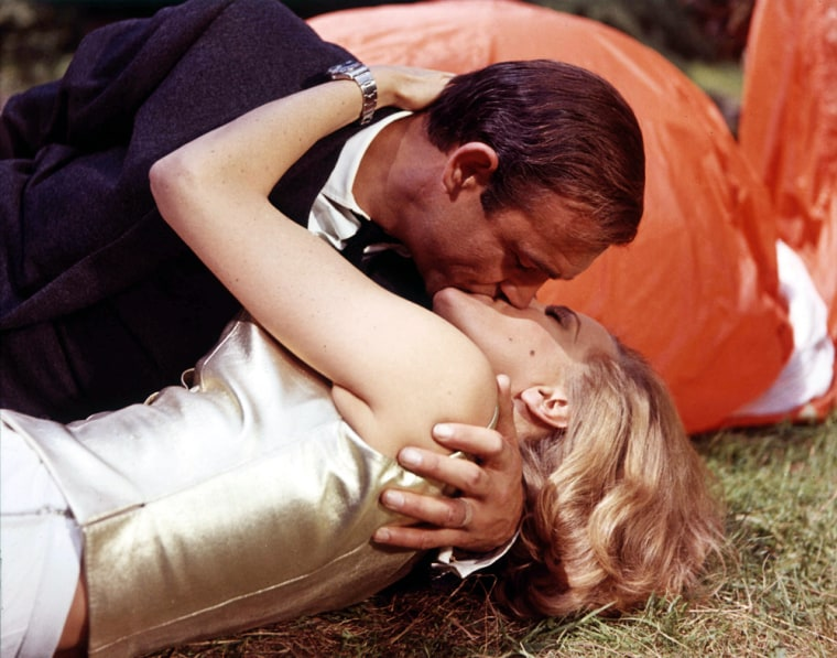 1964. A scene from the third film in the James Bond franchise, -Goldfinger. Pictured are James Bond, played by British actor Sean Connery, and Pussy Galore played by Honor Blackman in a passionate embrace.