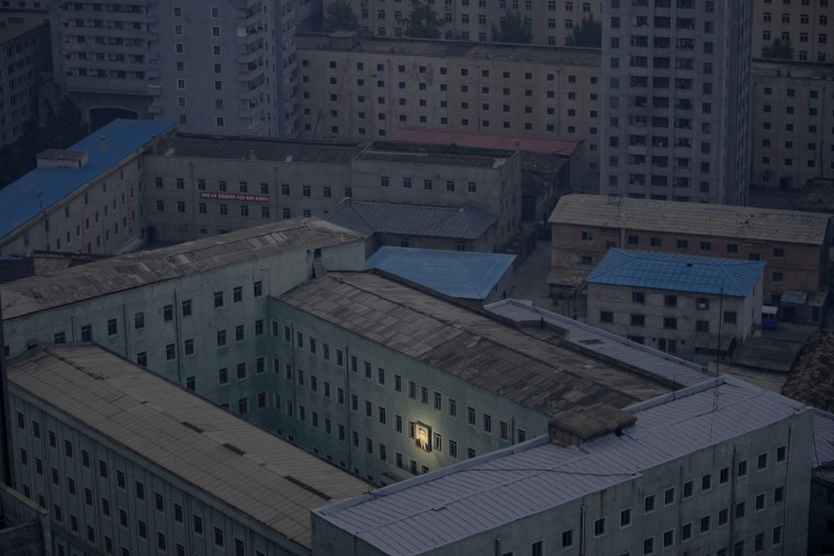 Image: Damir Sagolj has won the first prize Daily Life Singles with this photograph of a picture of North Korea's founder, Kim Il-sung, decorating a building in the capital Pyongyang