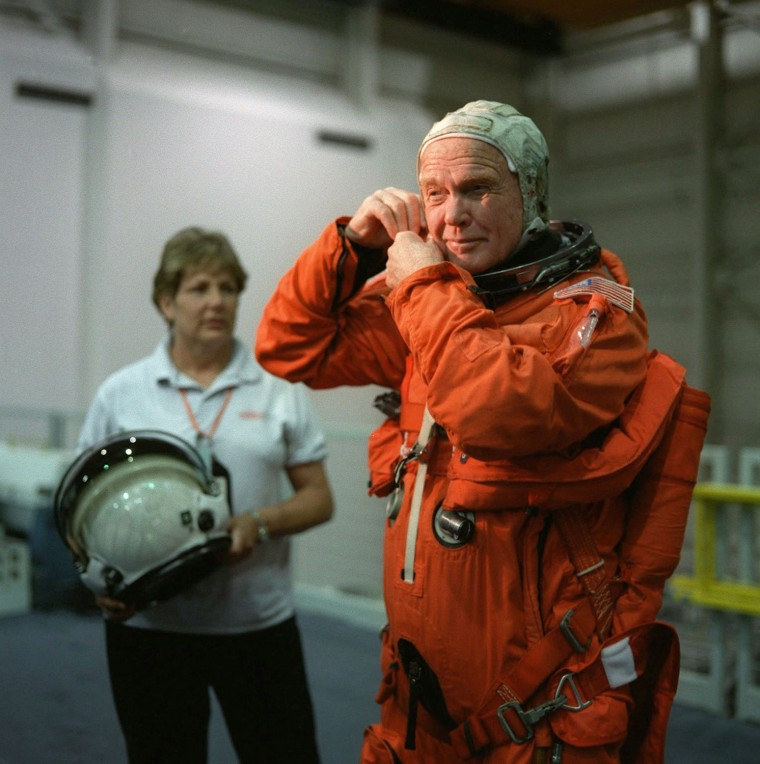Image: Sen. Glenn adjusts his space suit in training