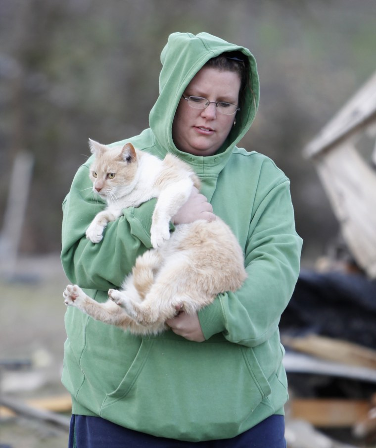 Image: Donna Jarvis holds Sunshine the cat after finding her following a tornado where several people died, in East Bernstadt, Kentucky