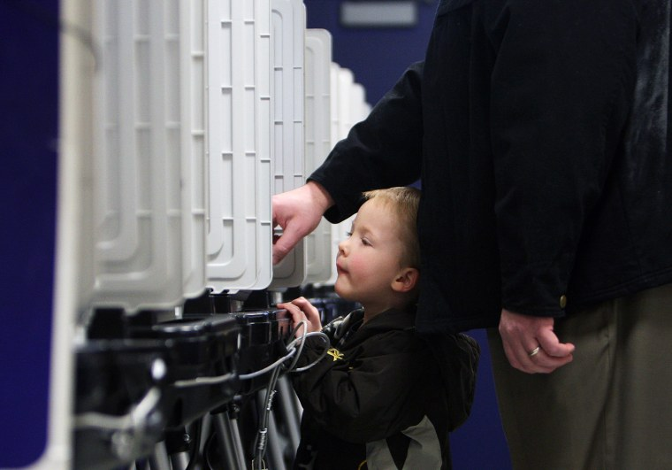 Image: Bradley Williams, 3, leans over to take a look as his dad, Doug, casts his vote during Super Tuesday