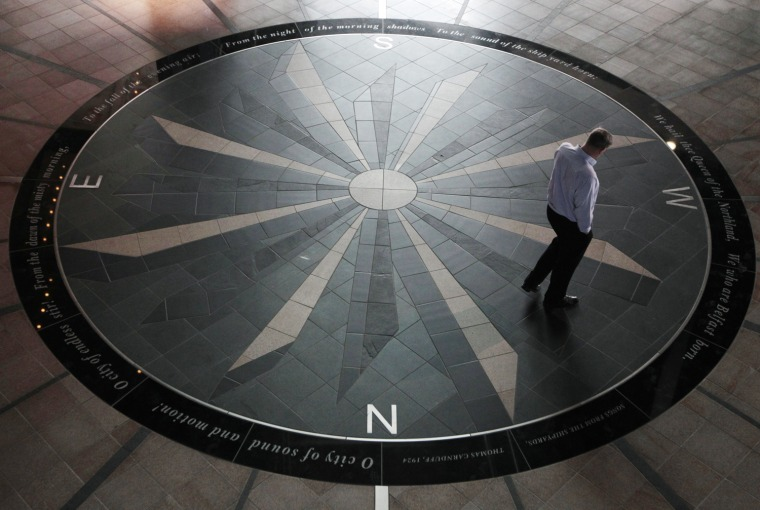 Image: A man walks over a compass design in the entrance of the Titanic Belfast building in Belfast