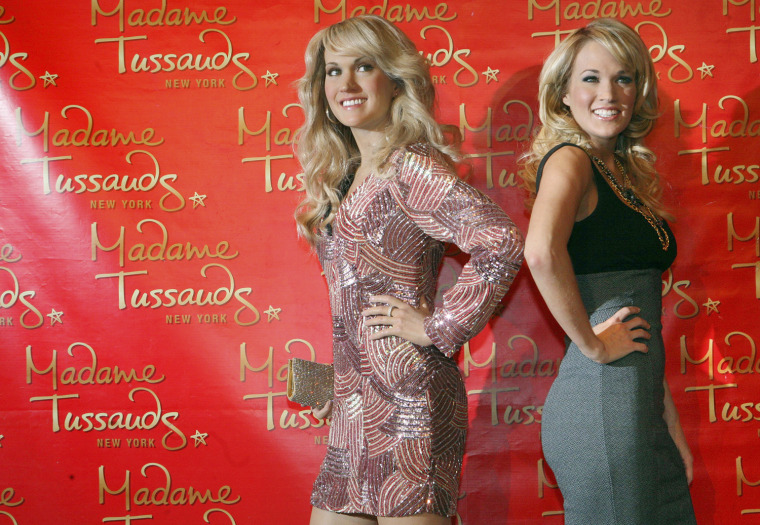 Image: Singer Carrie Underwood poses next to her wax figure after its unveiling at Madame Tussauds in New York