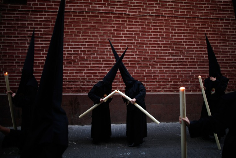Image: Penitents light their candles as they take part in the Calvario brotherhood procession during Holy Week in Malaga