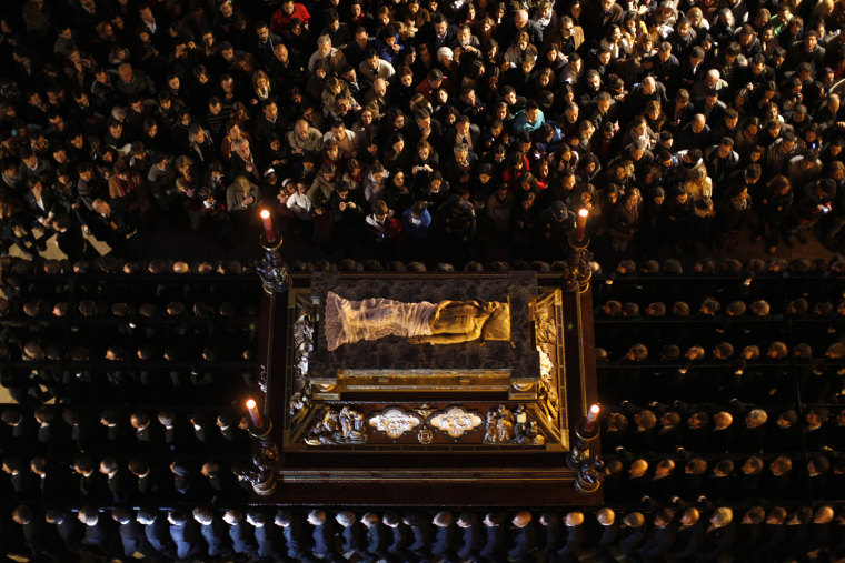 Image: People watch penitents carry throne with statue of Jesus Christ as they take part in Sepulcro brotherhood procession in Malaga