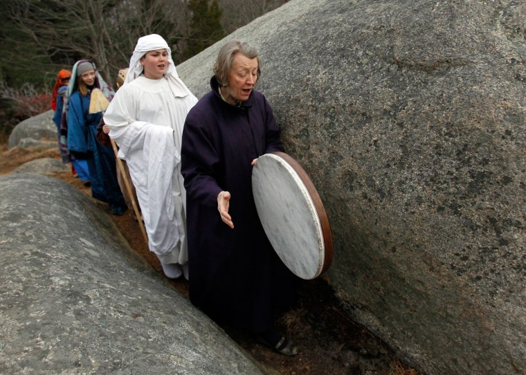 Image: Pastor Kathleen Adams leads members of the Schola Cantorum of the Annisquam Village Church through a path to celebrate Easter Sunday at Squam Rock