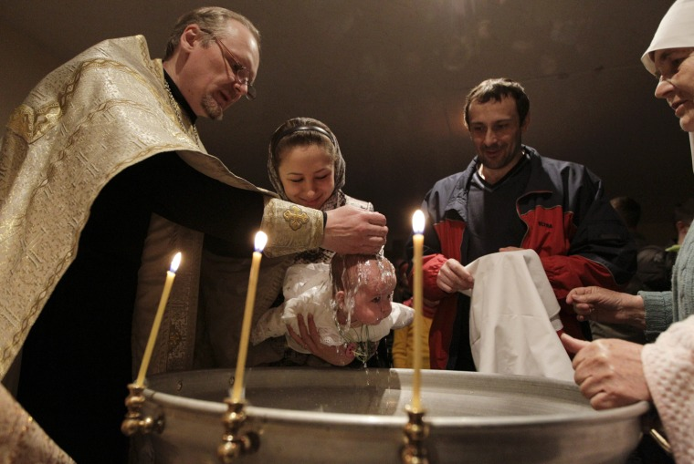 Image: An Orthodox priest baptizes a child in a church while believers celebrate Palm Sunday in Bobruisk
