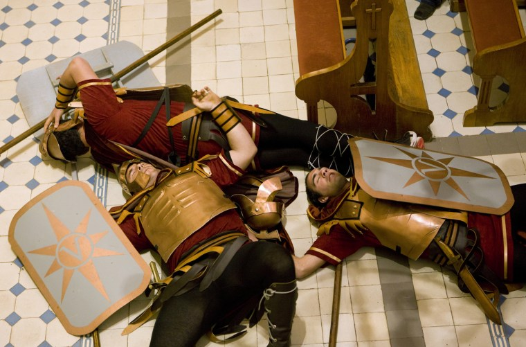 Image: Fishermen dressed as Roman soldiers collapse as they re-enact a scene from the Bible during mass as part of the Easter tradition at the church in the village of Sumartin