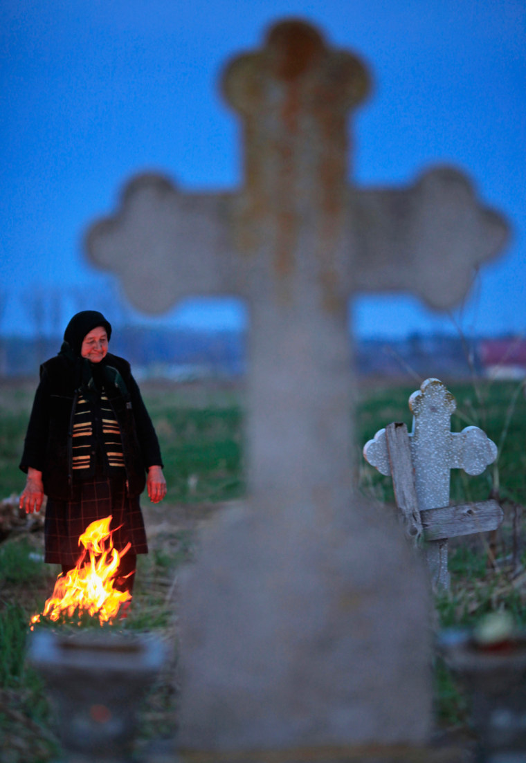 Image: A woman stands at the grave of a relative after bringing incense and flowers during the Orthodox Palm Sunday in Heresti cemetery