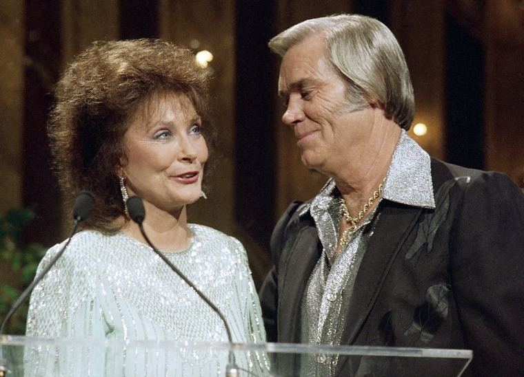 Country star George Jones, right, gets a hug from singer Loretta Lynn as he receives the Living Legend Award during the annual Music City News Country Awards, Monday, June 9, 1987, Nashville, Tenn. (AP Photo/Mark Humphrey)