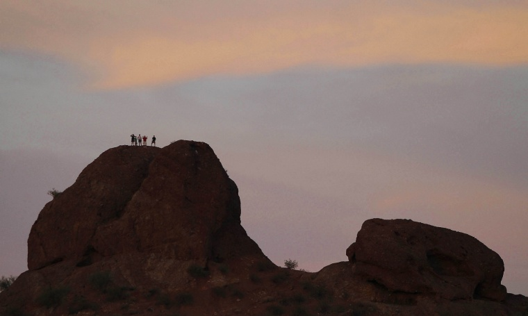 "Image: Men stand on top of a butte at Papago Park in Phoenix, Arizona, hoping for a better view of the ""super Moon"""