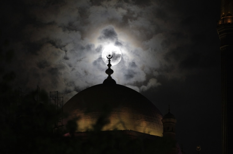 Image: A full moon is seen behind the minaret of Mohamed Ali mosque, in Islamic Cairo