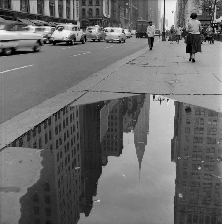 The reflection of the Chrysler Building is seen in a puddle on a sidewalk along 42nd Street in New York in April of 1954.