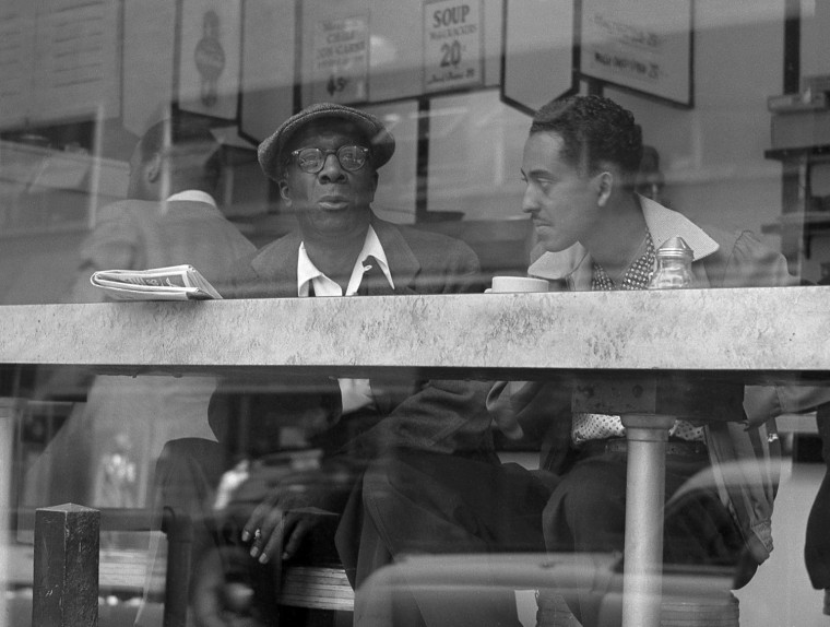 Two men have a conversation in a coffee show near Times Square in April of 1954.