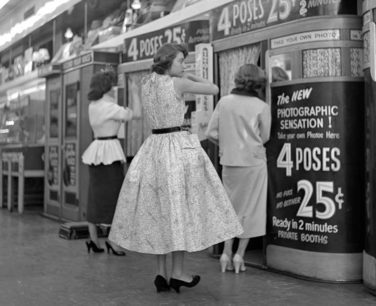 Three young ladies prepare to have their pictures taken in photo booths in Manhattan in April of 1954.